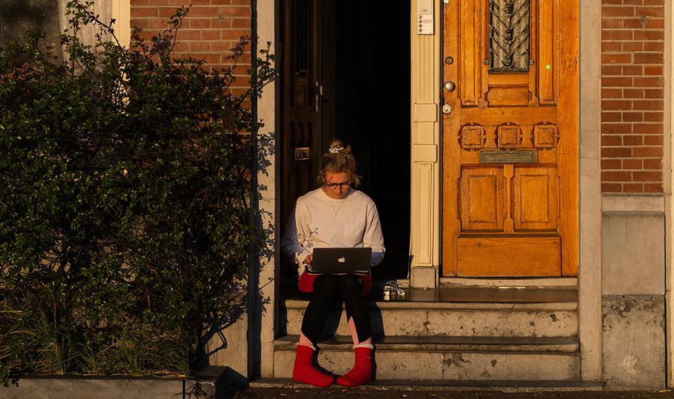 girl on doorstep looking at laptop